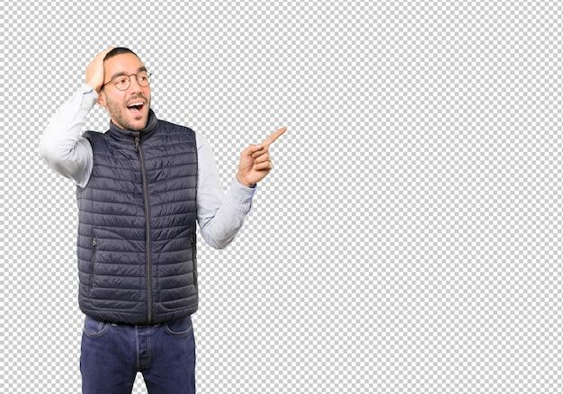 Koele jonge man wijzend met zijn vinger