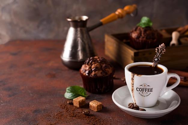 Kopje koffie met cooffee bonen, houten doos met korrels van koffie en specerijen, cupcake op een steen