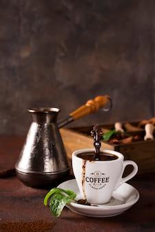 Kopje koffie met cooffee bonen, houten kist met korrels van koffie en specerijen, cezve op een steen