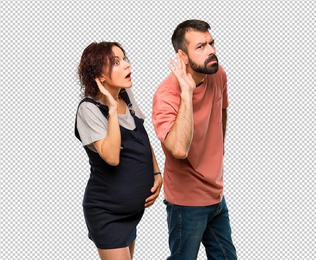 Koppel met zwangere vrouw die aan iets luistert door hand op het oor te zetten