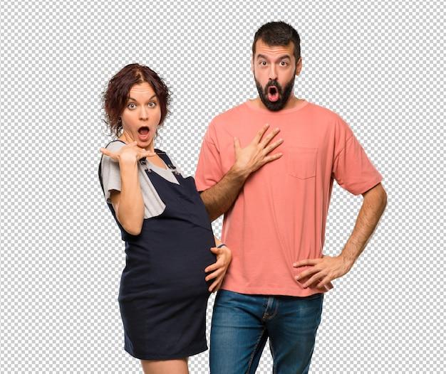 Koppel met zwangere vrouw verrast en geschokt. expressieve gezichtsemotie