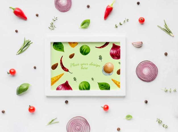 Kruiden mock-up frame omgeven door specerijen en plakjes groenten