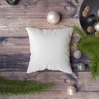 Kussen op een houten tafel omringd door kerstballen, dennen en sparren
