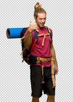 L'escursionista uomo con zaino in spalla montagna dando un pollice in alto gesto perché è successo qualcosa di buono
