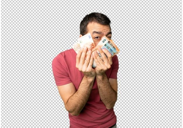 L'uomo prende un sacco di soldi che coprono gli occhi con le mani e guardando attraverso le dita