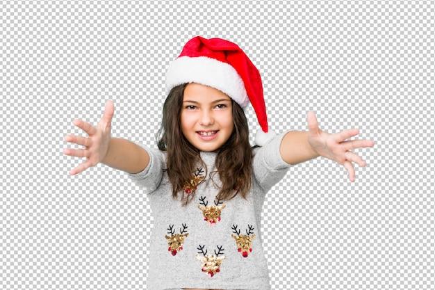 La bambina che celebra il giorno di natale si sente sicura dando un abbraccio alla fotocamera.