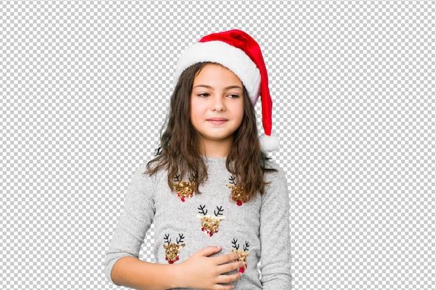 La bambina che celebra il giorno di natale tocca la pancia, sorride delicatamente, il cibo e il concetto di soddisfazione.