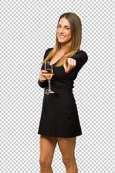 La donna con lo champagne che celebra il nuovo anno 2019 punta il dito verso di te con un'espressione fiduciosa