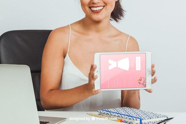 La donna di smiley con il ridurre in pani di tabella in ufficio
