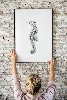 La foto del cavalluccio marino dell'illustrazione della mano sta appendendo sulla parete