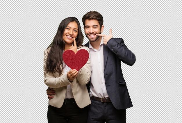 La giovane coppia in giorno di san valentino sorride, indicando la bocca