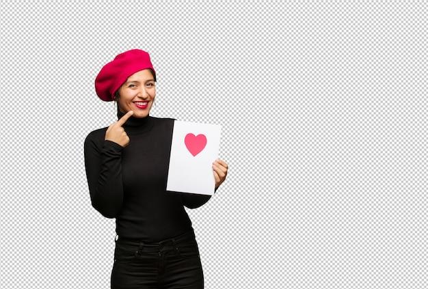 La giovane donna nel giorno di san valentino sorride, indicando la bocca