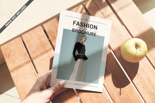 La mano della ragazza tiene una rivista sopra un mockup di tavolino