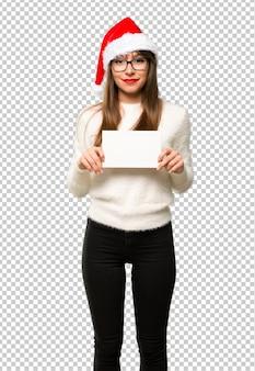 La ragazza con la celebrazione delle feste di natale che tengono un cartello bianco vuoto per inserisce un concetto