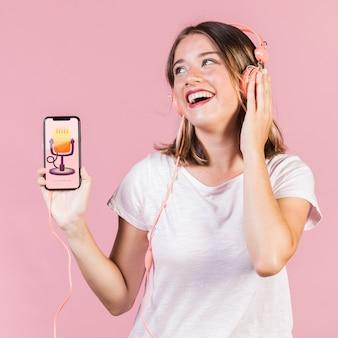 Lachende jonge vrouw die met hoofdtelefoons een cellphonemodel houdt