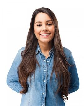 Lachende jonge vrouw met de handen op haar rug