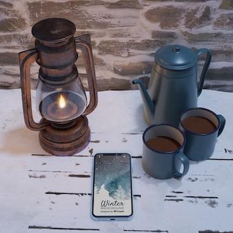 Lantaarn en waterkoker met hete thee naast mobiel