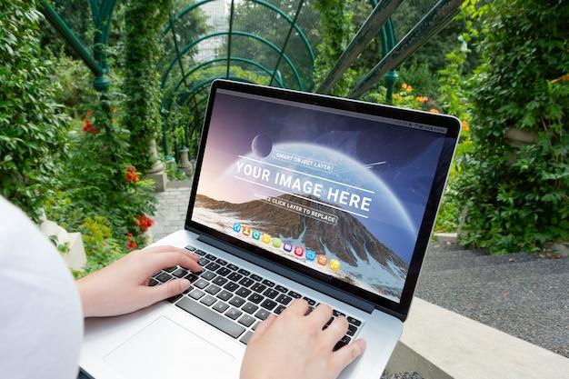 Laptop die vrouwenknieën in parkmodel legt