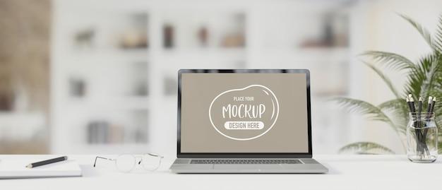 Laptop met mockup-scherm op tafel met briefpapier en bril 3d render