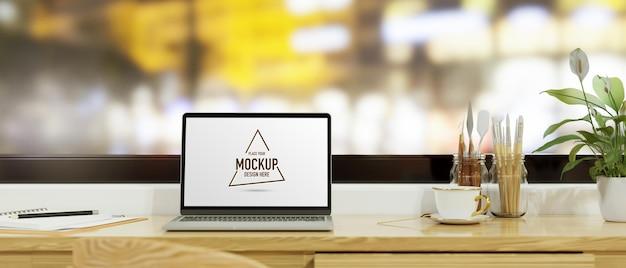 Laptop met mockup-scherm op tafel met verfgereedschap en briefpapier naast het raam