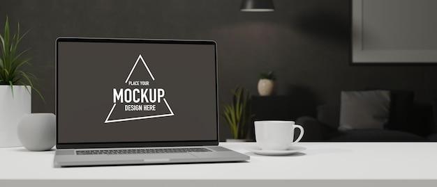 Laptop met mockup-scherm op witte tafel met een kopje en decoraties