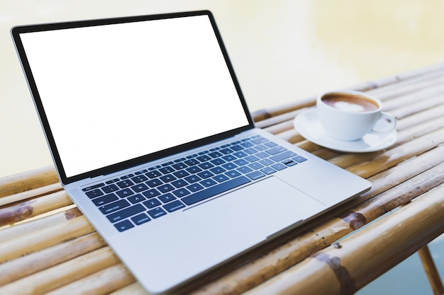 Laptop mockup en hete espresso in een witte koffiemok op een bamboelijst, openlucht