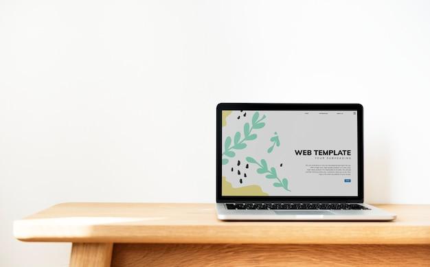 Laptop mostrando plantilla de página web en una mesa de madera