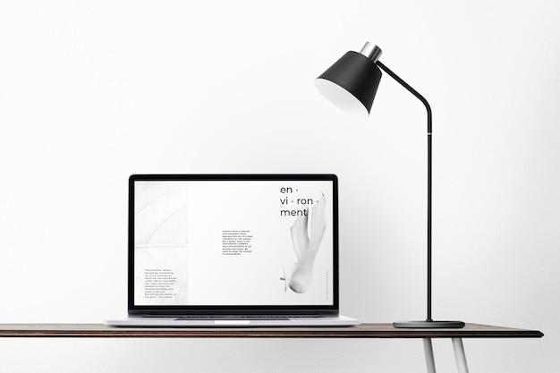 Laptop scherm mockup psd op een bureau minimaal thuiskantoor zone ontwerp