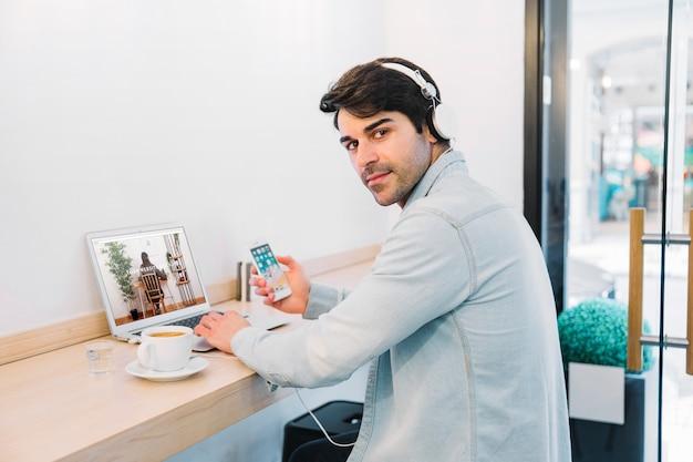 Laptopmodel met de mens die hoofdtelefoons draagt