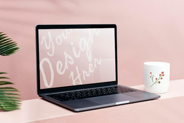 Laptopmodel met een pastelroze muur