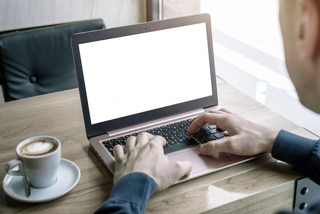 Laptopmodel voor promotie van app- of websiteontwerp. de man in de caffee gebruikt een laptop die op een toetsenbord typt. kopje koffie naast