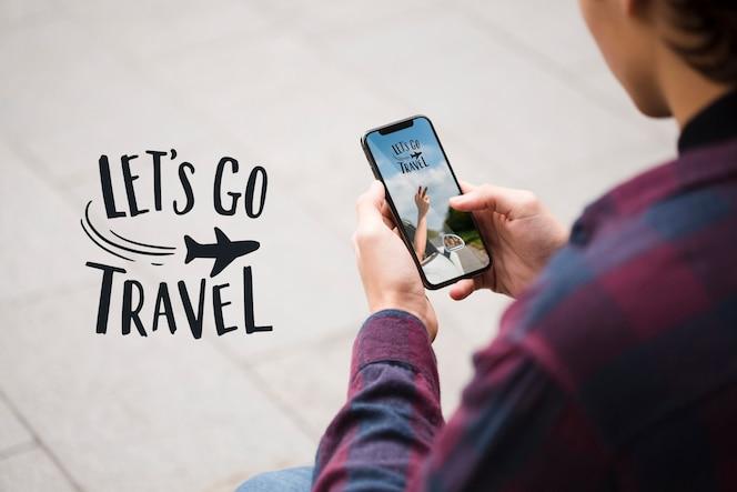 Laten we gaan reizen en man kijkt naar zijn telefoon over het schouderschot