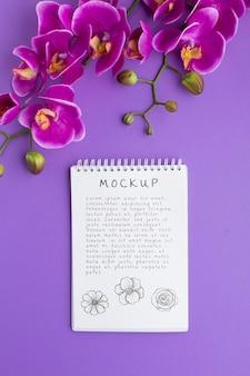 Lay piatto di notebook mock-up con orchidea