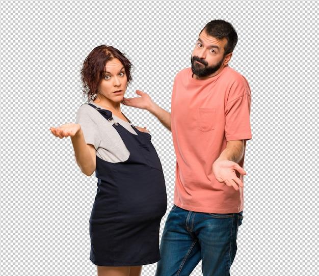 Le coppie con la donna incinta che fa i dubbi gesture mentre sollevano le spalle