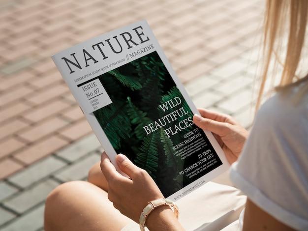 Le mani posteriori di vista che tengono la rivista della natura deridono su