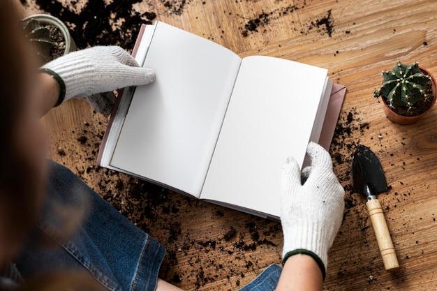 Leeg boek mockp psd in de handen van een tuinman