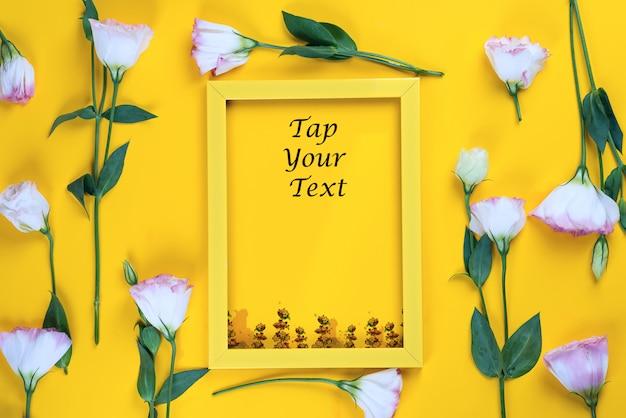 Leeg geel kader en bloemeneustoma als laag op geel papier