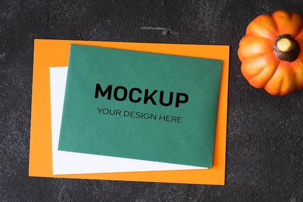Leeg groenboek voor mock-up sjabloonontwerp en decoratieve pompoen op donkere betonnen achtergrond. uitzicht van boven. platliggend, bovenaanzicht, overhead, kopieerruimte