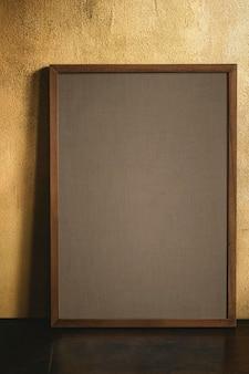 Leeg houten frame door een grunge gele muur