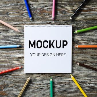 Leeg notitieboekje en kleurrijke potloden op de houten lijst. paper achtergrond. mock up. uitzicht van boven