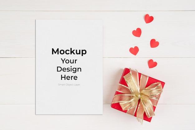 Lege briefkaart en geschenkdoos en hartvorm op houten tafel