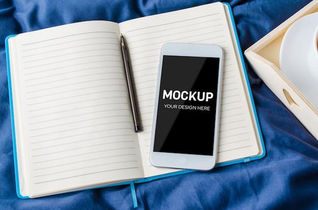 Lege smartphone scherm, notebook en kopje koffie op een dienblad op het bed