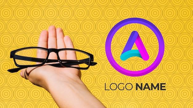 Lente de marco negro con el nombre del logotipo de la empresa y la mano