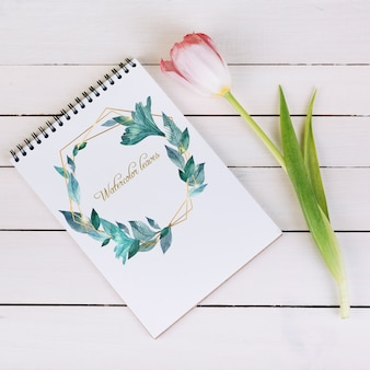 Lente notebook mockup met decoratieve plant in bovenaanzicht
