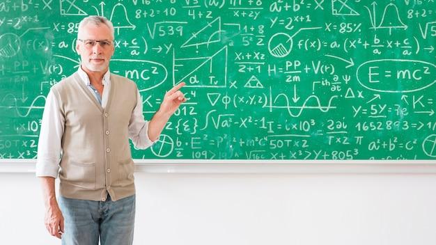 Leraar wijzend op bord met wiskundige formules
