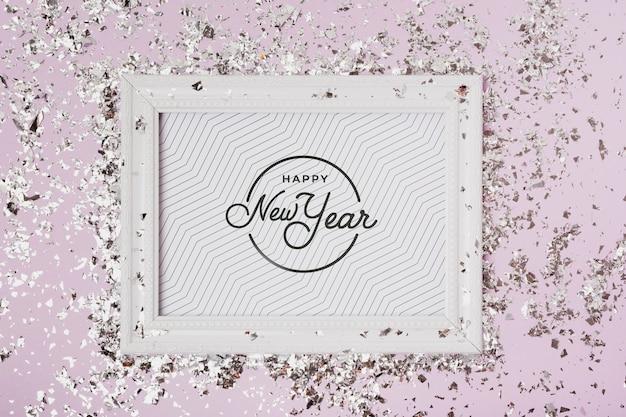 Letras de año nuevo en maqueta de marco con confeti