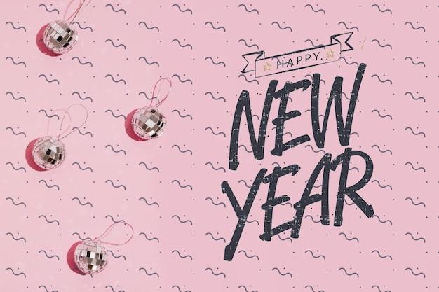 Letras de año nuevo con pequeños adornos de bolas de discoteca