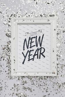 Letras planas de año nuevo en maqueta de marco con confeti