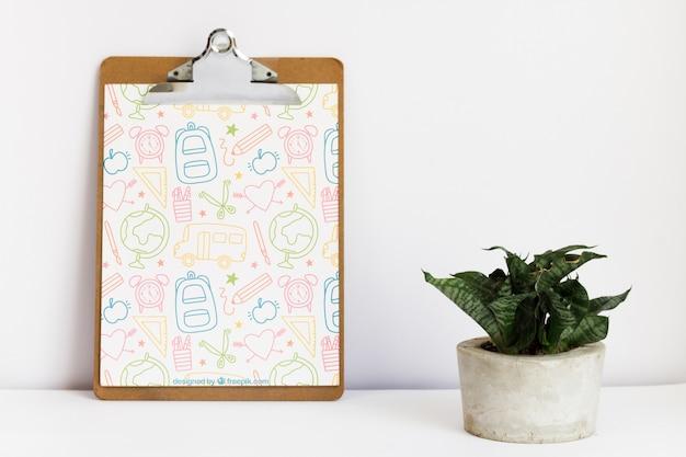 Leunend klembord naast een plant