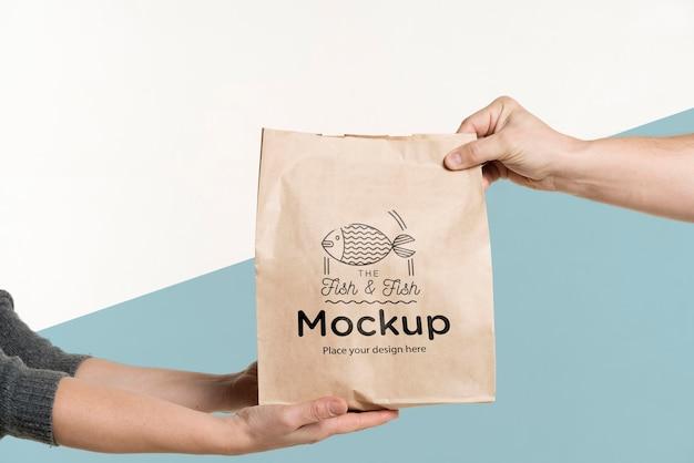 Levering man een zak met voedsel overhandigen aan een klant